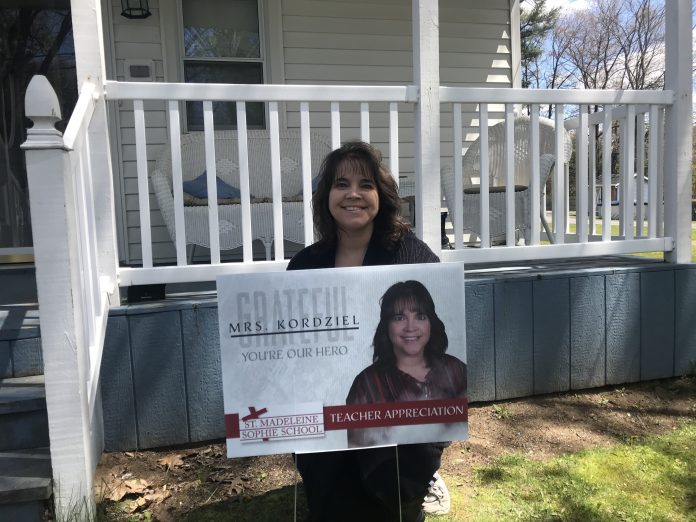 Mrs. Kordziel, a teacher at a private school in Schenectady, New York, stands by a sign recognizing her hard work. Thanks to routing provided by Transfinder, school principal Kelly Sloan hand-delivered signs to each of her teachers for display in their front yards.