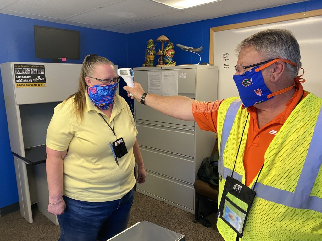 A Denver Public Schools transportation employee checks his coworker's temperature with a contactless thermometer.