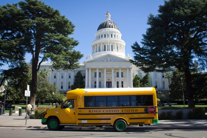 A March 2014 file photo of an early electric school bus parked in front of the state capitol building in Sacramento, California. (Source: Wikimedia Commons/Urvashi Nagrani)