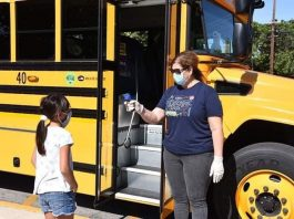 A staff member at Fullerton School District in California checking a child's temperature prior to them boarding the school bus. (Photo courtesy of Fullerton SD.)