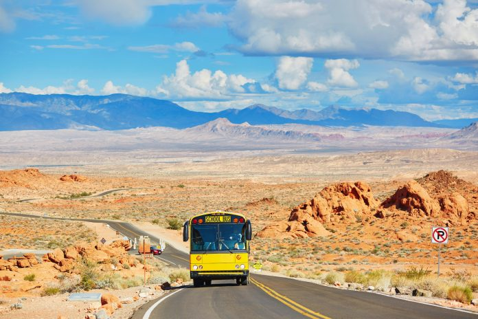 School bus driving on winding road in Valley of the Fire national park in Nevada, USA