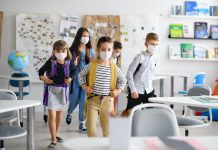 Group of children with face mask back at school after covid-19 quarantine and lockdown, entering classroom.
