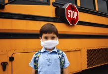 Coronavirus school reopening concept. A boy student stands in front of school bus wearing a face mask and backpack with stop sign clearly visible.