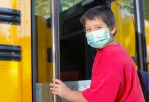 boy with COVID-19 mask boards school bus