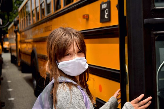 Girl with facemask boarding a school bus