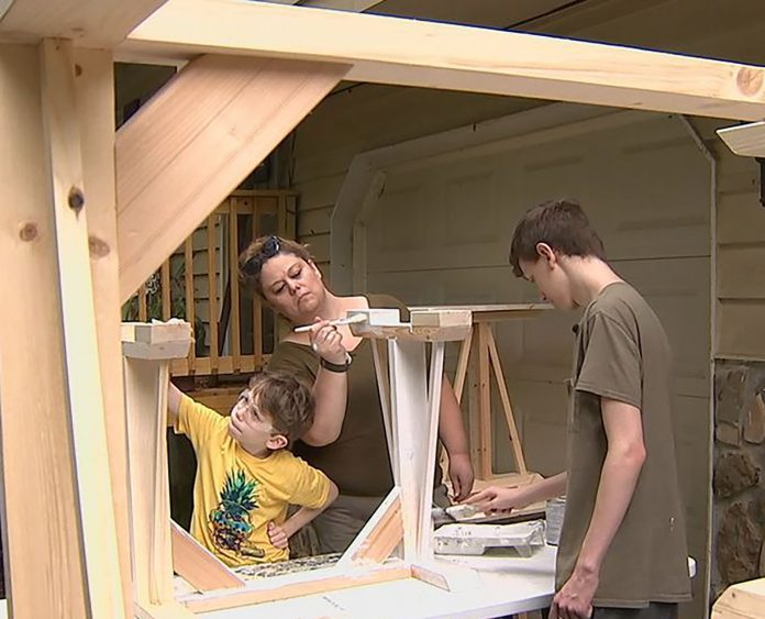 Michelle Minor and her two sons build desks for students who are online learning during the coronavirus pandemic. (Photo courtesy of Michelle Minor.)