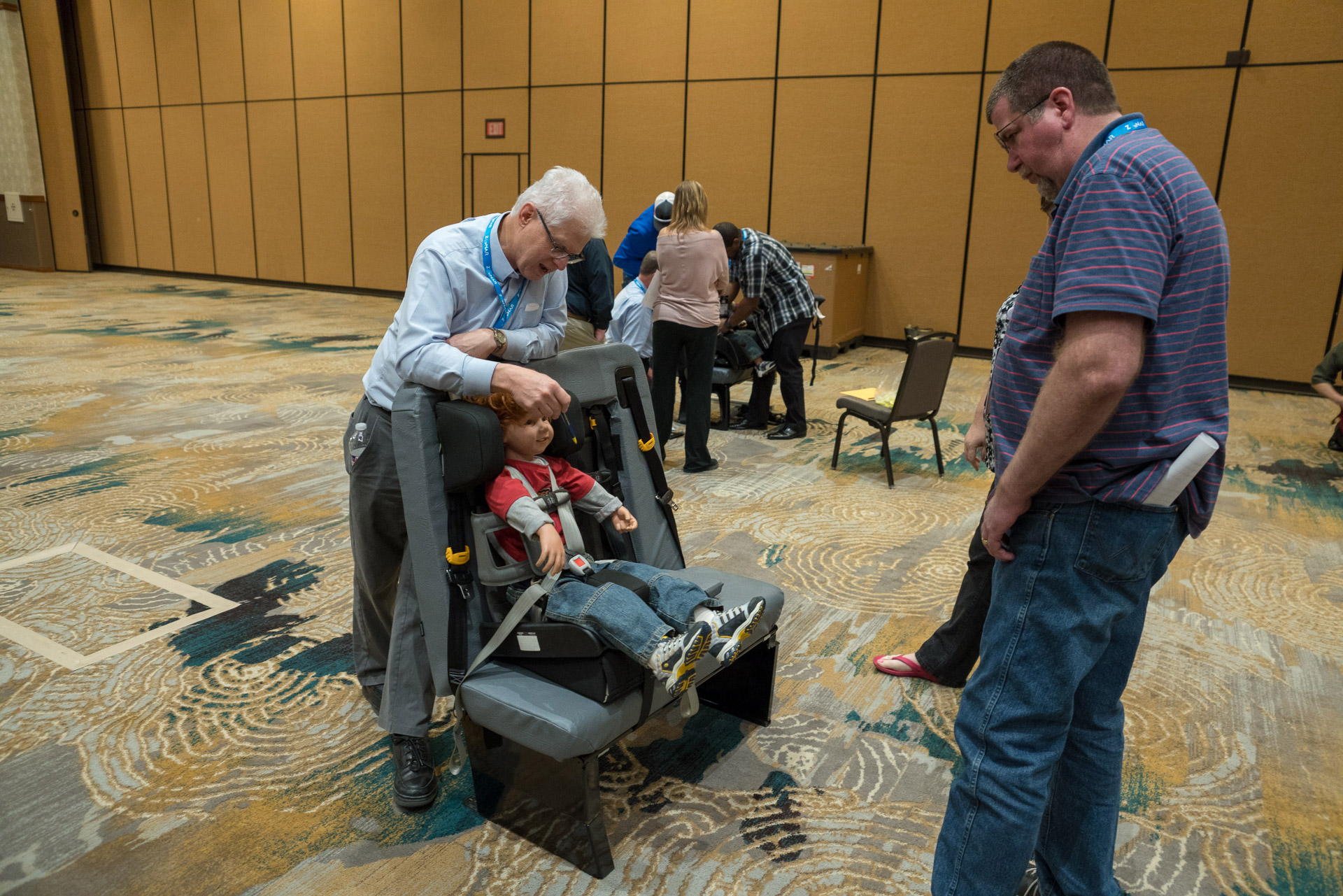 Charles Vits shows attendees of the 2018 TSD Conference the correct procedure for securing a student in a forward-facing car seat on a school bus.