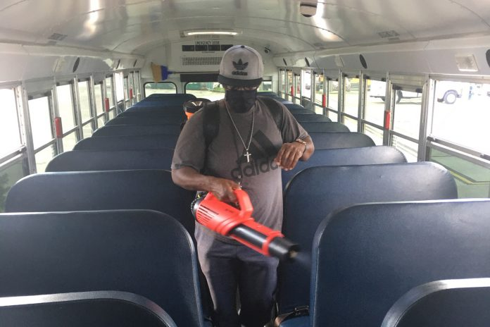An employee of the County School District of Indian River operates an eMist disinfectant sprayer after a route.