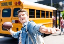happy teen schoolboy throwing american football ball in front of school bus
