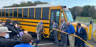 Local media photograph the cutting of a ribbon by officials of Thomas Built Buses, Dominion Energy and dealer Sonny Merryman, as they welcome the first electric school buses to Virginia during an event on Tuesday, Oct. 27, 2020.
