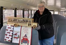 """Marsha Birkholz, a school bus driver for, Forrestville Valley CUSD 221 in Illinois, poses with decorations she placed on the seat directly behind her. The seat must remain empty in compliance with COVID-19 guidelines. The theme on Dec. 17 was """"All Roads Lead Home to Christmas."""""""