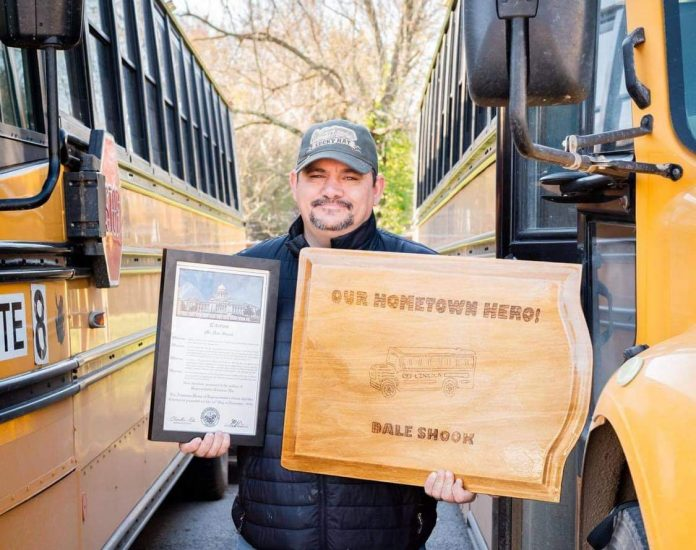 Dale Shook, school bus driver at Lincoln Consolidated School District in Michigan, stands with the two plaques he received for protecting siblings during a right-side illegal passing incident last fall.
