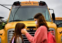 Female child helping another with a facemask in front of school bus