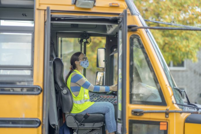 Female bus driver wearing a protective face mask and shield while driving a school bus during COVID-19 to avoid the transfer of germs.