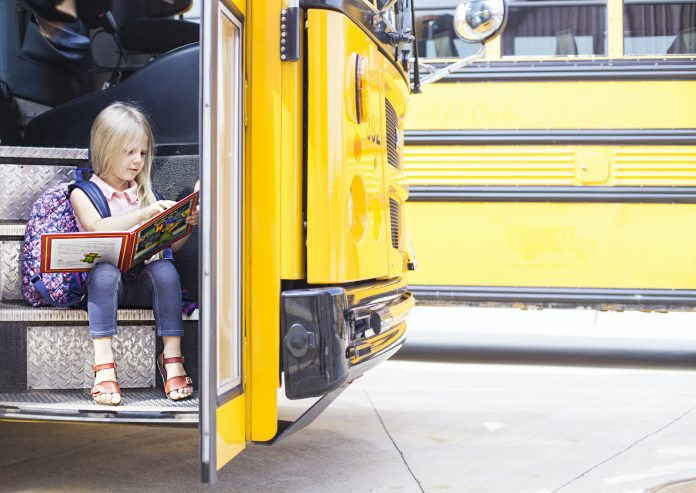 Schoolgirl sitting in school bus and reading the book. Back to school or education concept