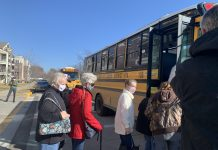 Resident of a long-term care facility board North Kansas City school buses to be transported to a COVID-19 vaccination site.