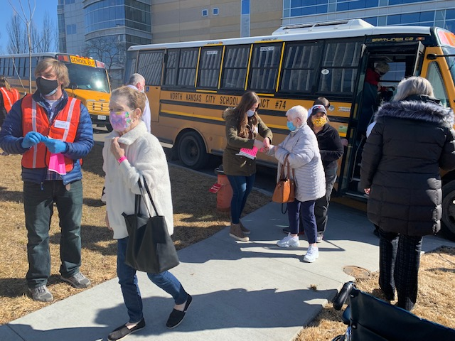 Residents exit a school bus on their way to get vaccinated.