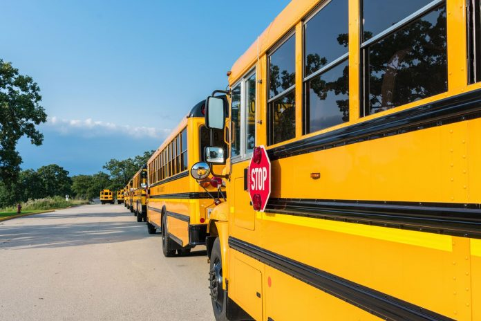 Long row of yellow school buses lined up in the parking lot ready to pick up students
