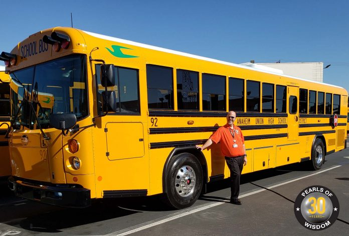 Matthew Thomas, the director of transportation at Anaheim Union High School District in Southern California, poses with a school bus. Thomas is going on 25 years in the industry and recently reinvented himself.