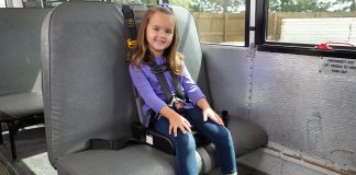 Preschool student sits in a booster seat approved for use in school buses.