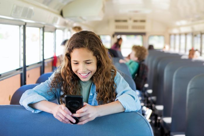 As she waits to get off the bus, a girl smiles when she reads the text message her older sister sent that morning.
