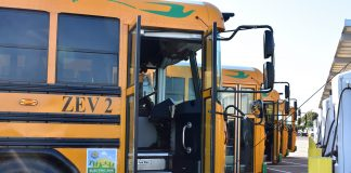 A row of electric school buses charge at Stockton Unified School District in California.
