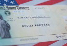 Washington, DC, USA - March, 16, 2020: COVID-19 economic Stimulus check on blurred USA flag background. Relief program concept. Banner photo.