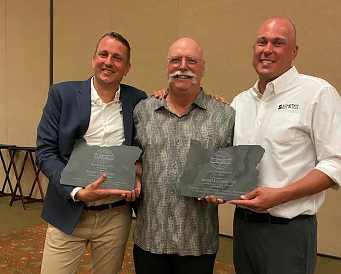 From left: Chase Schetky, co-owner of Schetky NW Bus Sales; Michael Shields, retired Director of Transportation from Salem-Keizer SD; and David Schetky, co-owner of Schetky NW Bus Sales received the 2020 Ron Bryan President's Award during the Oregon Pupil Transportation Association Conference. David and Chase accepted the award for their father, Randy Schetky, who died on April 3, 2020.