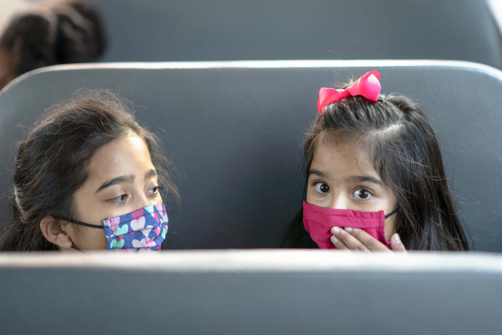 children in bus seat look back
