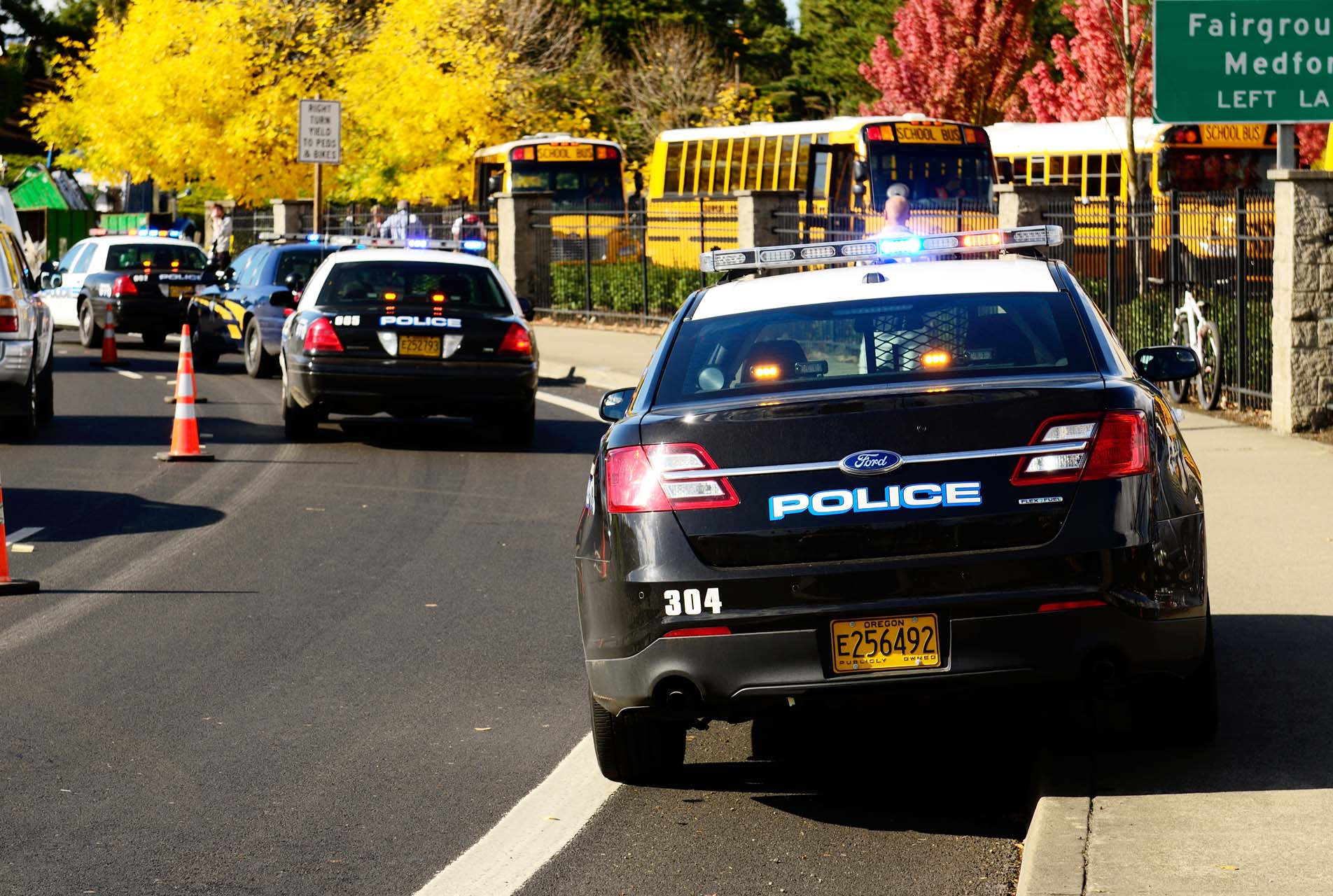 Roseburg Oregon - October 16, 2012: Police cars and school buses at an accident scene at the entrance of the High School loading zone.