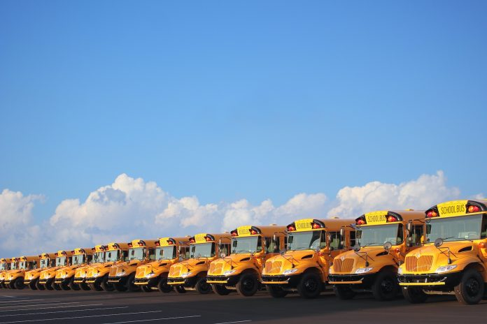 Row of school buses on sunny day with clouds and blue sky